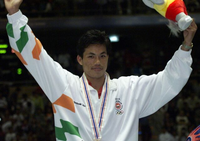 India's Ng-Dingko Singh celebrates on the podium after winning gold in the bantam weight boxing finals at the 13th Asian Games in Bangkok 17 December