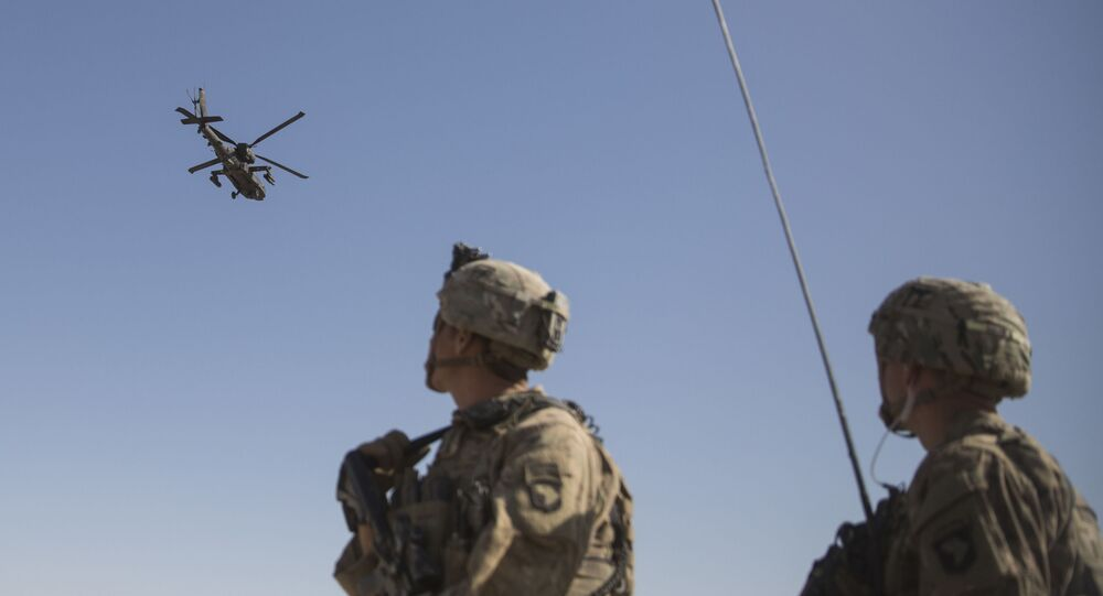 This June 10, 2017 photo released by the U.S. Marine Corpsshows an AH-64 Apache attack helicopter provides security from above while CH-47 Chinooks drop off supplies to U.S. Soldiers with Task Force Iron at Bost Airfield, Afghanistan.