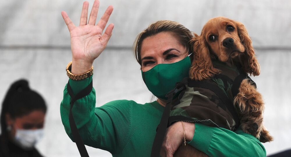 Bolivia's interim President Jeanine Anez, wearing a mask amid the new coronavirus pandemic, carries her dog as she greets people during an announcement to create a shelter for abandoned animals in La Paz, Bolivia, Sunday, Sept. 20, 2020.