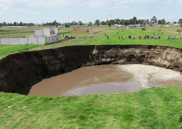 An aerial view of a sinkhole found in a farmland in Santa Maria Zacatepec, Puebla, Mexico May 30, 2021 is shown in this screen grab obtained from a social media video.