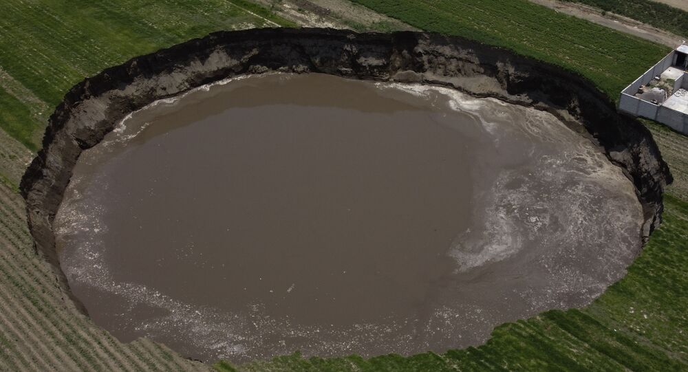 A water filled sinkhole grows in Zacatapec, on the outskirts of Puebla, Mexico, Tuesday, June 1, 2021. The massive water-filled sinkhole continues swallowing farmers' fields in the central Mexican state of Puebla.