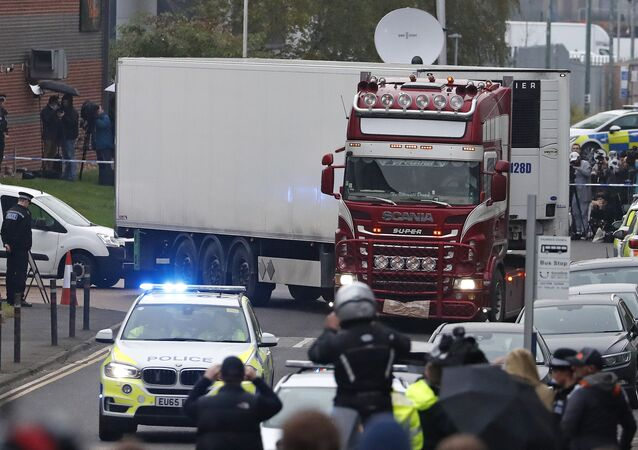 In this Wednesday Oct. 23, 2019 file photo, police escort the truck, that was found to contain a large number of dead bodies, as they move it from an industrial estate in Thurrock, south England