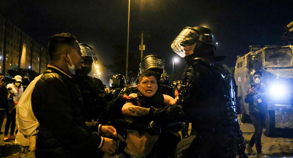 A demonstrator is trying to prevent a fellow demonstrator to be detained by police during protests for policy reforms and against the government, in Bogota, Colombia May 21, 2021. Picture taken May 21, 2021.