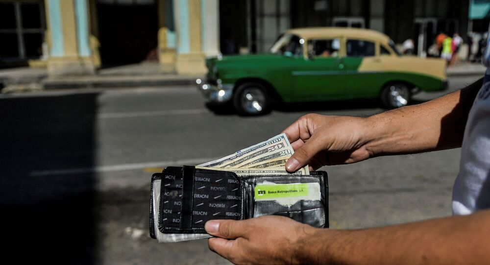 A man shows his wallet with US dollars in it in a street of Havana, on September 15, 2020