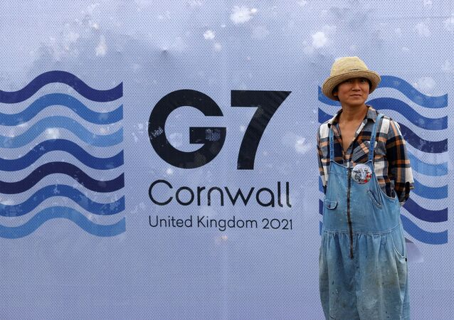 A pedestrian poses for a photograph with a G7 logo outside the media centre at Falmouth, Cornwall on June 10, 2021, ahead of the three-day G7 summit being held from 11-13 June