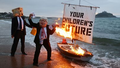 Activists from the climate action group Ocean Rebellion set a boat on fire during a demonstration at sunrise on Marazion Beach, Cornwall, Britain, 5 June 2021, ahead of the G7 summit in Carbis Bay, Cornwall.