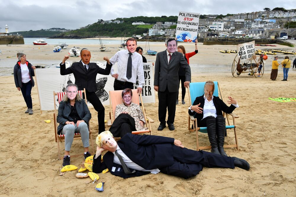 Climate change activists wear masks representing world leaders during a protest in St Ives, on the sidelines of the G7 summit in Cornwall, Britain, 11 June 2021.