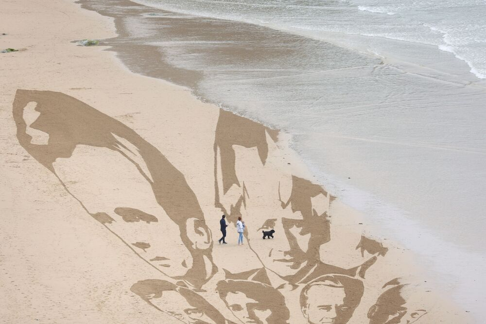 An incoming tide washes away part of a giant beach sand artwork depicting the faces of the G7 leaders, created by campaign group Avaaz, on Watergate Bay Beach, Newquay, Britain, 10 June 2021.