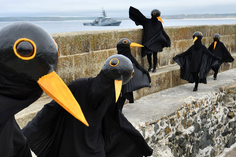 Climate change activists dressed up as black birds protest in St Ives, on the sidelines of the G7 summit in Cornwall, Britain, 11 June 2021.