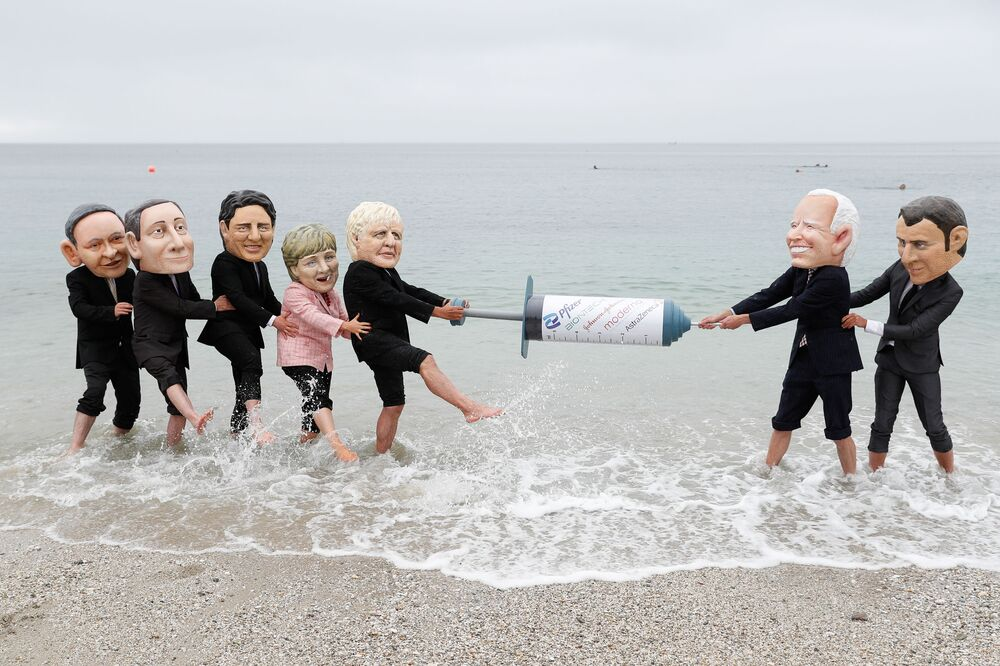 Oxfam activists with Big Heads caricatures of US President Joe Biden and France's President Emmanuel Macron pretend to fight over a COVID-19 vaccine with Japan's Prime Minister Yoshihide Suga, Italy's Prime Minister Mario Draghi, Canada's Prime Minister Justin Trudeau, German Chancellor Angela Merkel, and Britain's Prime Minister Boris Johnson, during a protest at a beach near Falmouth, on the sidelines of the G7 summit in Cornwall, Britain, 11 June 2021.