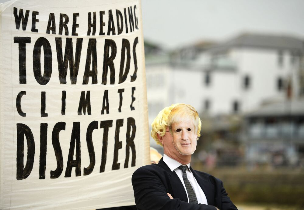 An environmental activist from Extinction Rebellion wearing a face mask of Britain's Prime Minister Boris Johnson takes part in a photocall in St Ives on 11 June 2021 during the G7 summit.