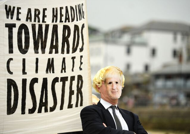 Environmental activist from Extinction Rebellion wears a face masks of Britain's Prime Minister Boris Johnson takes part in a photocall in St Ives on June 11, 2021 during the G7 summit.