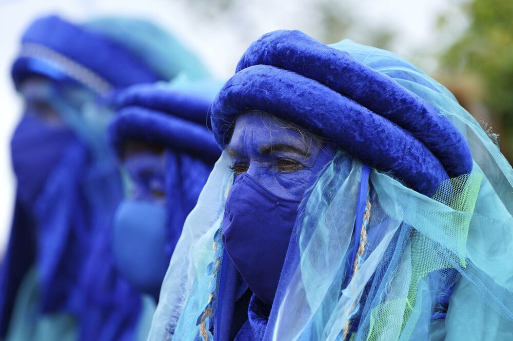 Climate activists dressed in blue costumes as they demonstrate near the G7 meeting taking place in St Ives, Cornwall, Britain, Friday, 11 June 2021. Leaders of the G7 begin their first of three days of meetings on Friday in Carbis Bay, in which they will discuss COVID-19, climate, foreign policy, and the economy.