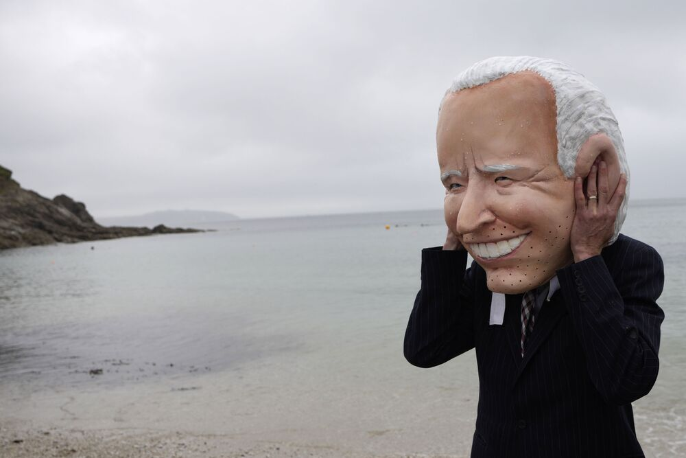 An activist wearing a giant head of US President Joe Biden prepares to take part in an NGO action over COVID-19 vaccines on Swanpool Beach in Falmouth, Cornwall, Britain, Friday, 11 June 2021.