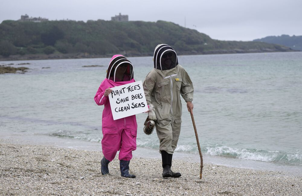 Climate activists Delores and Leroy Tycklemore wear bee keeping suits as they demonstrate as part of Fridays for Future on Gyllyngvase Beach in Falmouth, Cornwall, Britain, Friday, 11 June 2021.