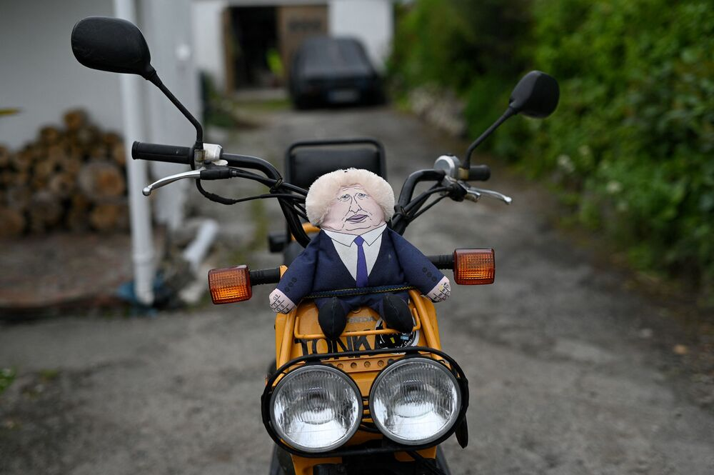 A caricature of Britain's Prime Minister Boris Johnson is pictured between the handle bars of a motorbike in Carbis Bay, Cornwall on 10 June 2021.