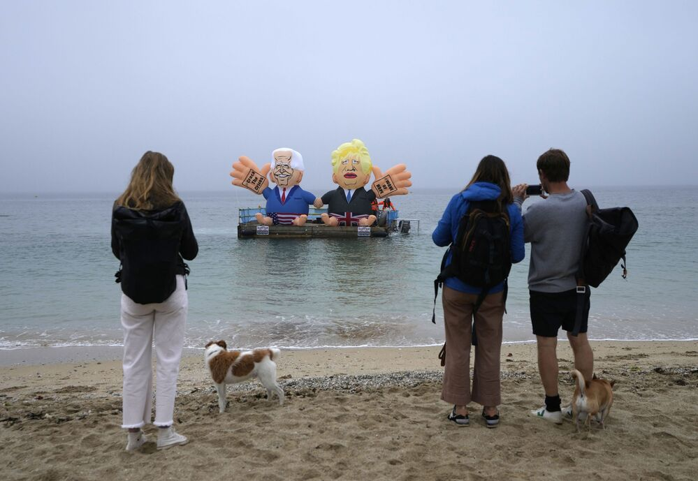 People watch from the beach as two giant balloons, depicting US President Joe Biden, left, and British Prime Minister Boris Johnson, float on a dock in Falmouth Harbour, Cornwall, Britain, during an action by NGOs on Friday, 11 June 2021.