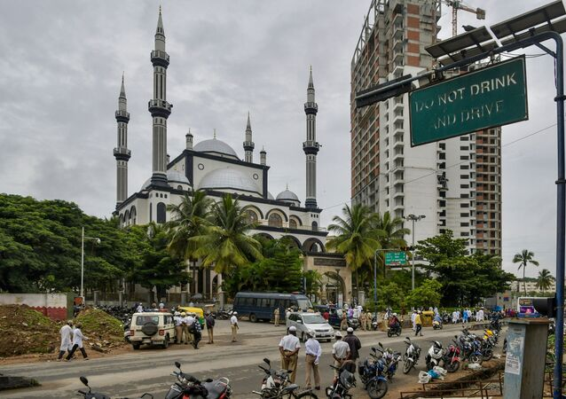 Police personnel stand on the road in front of Masjid-e-Eidgah Bilal as Muslim devotees arrive to offer prayers during the Eid al-Adha, the feast of sacrifice, in Bangalore on August 1, 2020