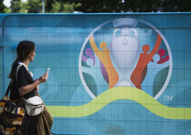 A pedestrian walks past the logo of the UEFA EURO 2020 European Football Championship in Copenhagen, one of the tournament's host cities, on June 10, 2021