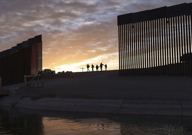 A pair of migrant families from Brazil pass through a gap in the border wall to reach the United States after crossing from Mexico in Yuma, Ariz., Thursday, June 10, 2021, to seek asylum.