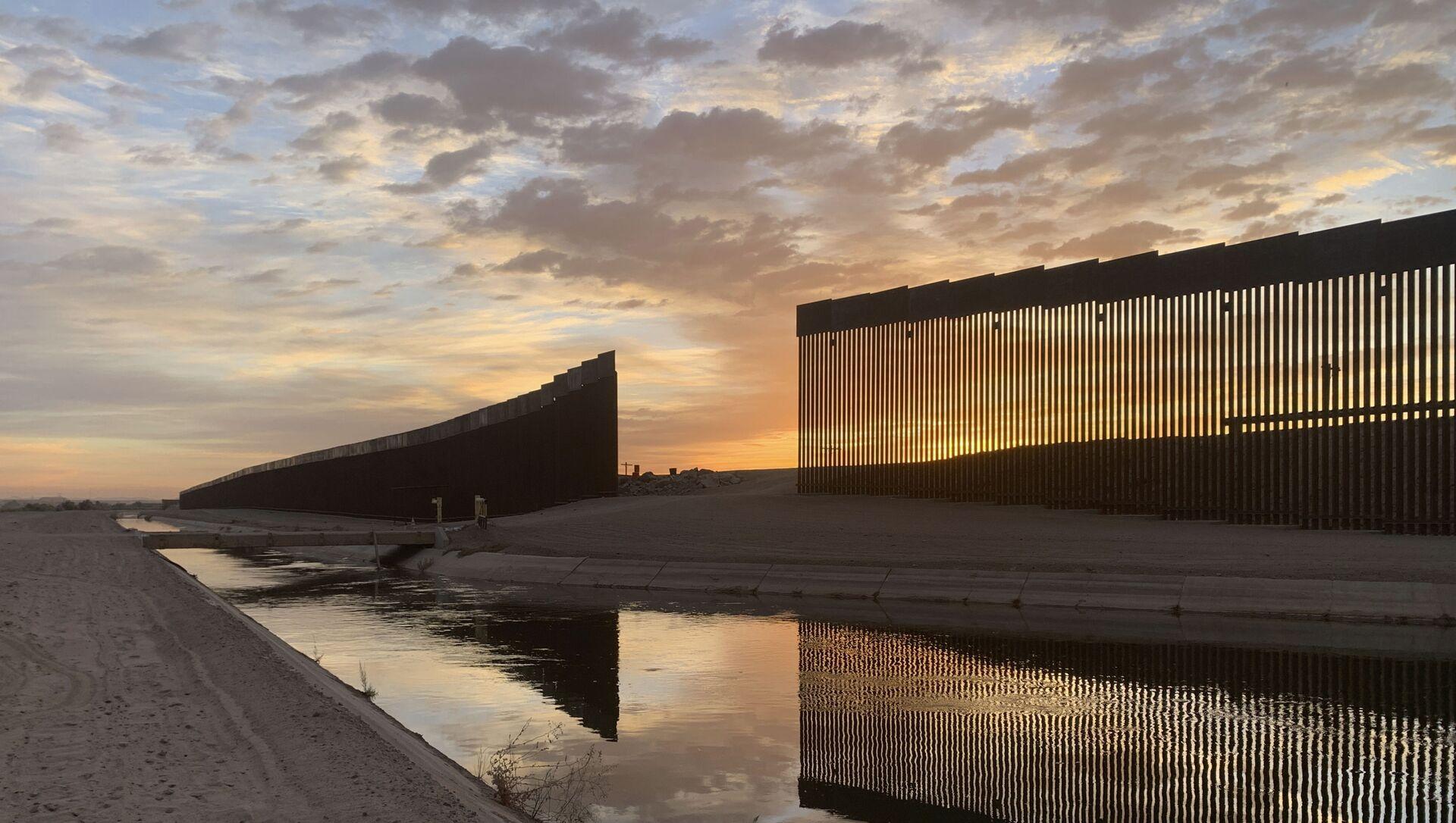 The sun sets above the U.S.-Mexico border wall, seen in Yuma, Ariz., Wednesday, June 9, 2021. - Sputnik International, 1920, 23.07.2021