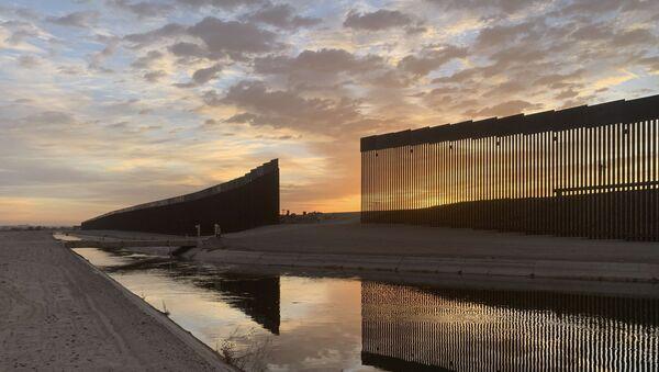 The sun sets above the U.S.-Mexico border wall, seen in Yuma, Ariz., Wednesday, June 9, 2021. - Sputnik International