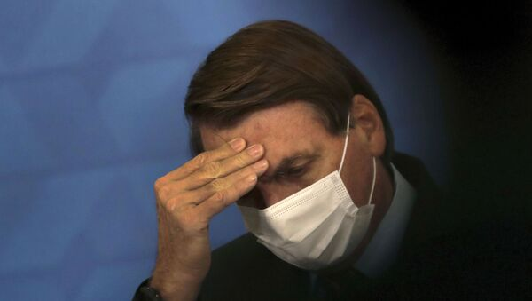 Brazil's President Jair Bolsonaro, wearing protective face mask, listens during a ceremony announcing economic measures to support philanthropic hospitals and help them treat COVID-19 patients, at the Planalto Presidential Palace, in Brasilia, Brazil, Thursday, March 25, 2021. - Sputnik International