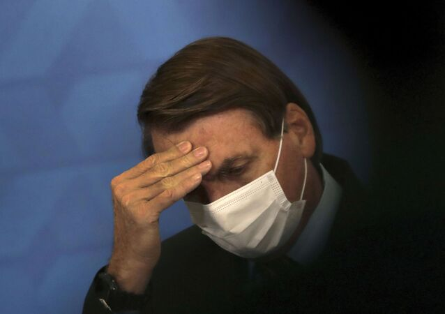 Brazil's President Jair Bolsonaro, wearing protective face mask, listens during a ceremony announcing economic measures to support philanthropic hospitals and help them treat COVID-19 patients, at the Planalto Presidential Palace, in Brasilia, Brazil, Thursday, March 25, 2021.