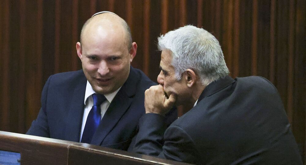 Israel's Yamina party leader, Naftali Bennett (L), smiles as he speaks to Yesh Atid party leader, Yair Lapid, during a special session of the Knesset, Israel's parliament, to elect a new president, in Jerusalem on June 2, 2021.