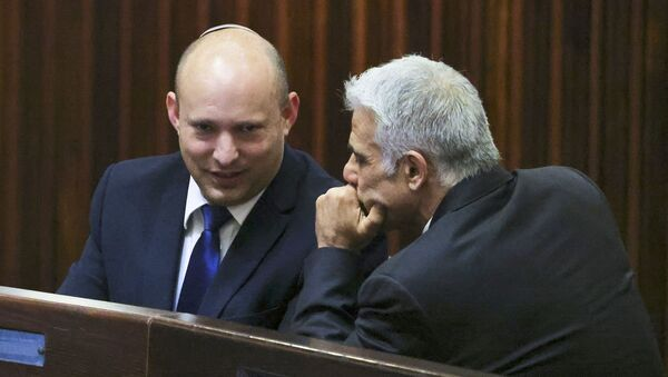 Naftali Bennett (L), smiles as he speaks to Yesh Atid party leader, Yair Lapid, during a special session of the Knesset, Israel's parliament, to elect a new president, in Jerusalem on June 2, 2021. - Sputnik International