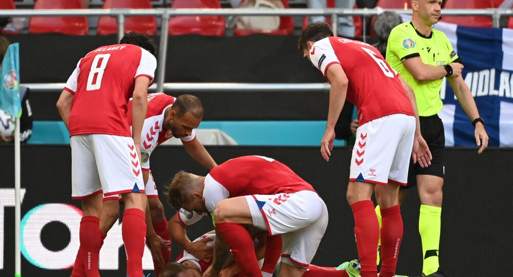 Denmark players help Denmark's midfielder Christian Eriksen after he collapsed before the medics arrive during the UEFA EURO 2020 Group B football match between Denmark and Finland at the Parken Stadium in Copenhagen on 12 June 2021
