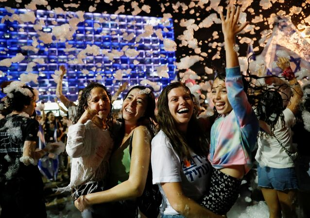 People celebrate after Israel's parliament voted in a new coalition government, ending Benjamin Netanyahu's 12-year hold on power, at Rabin Square in Tel Aviv, Israel June 13, 2021.