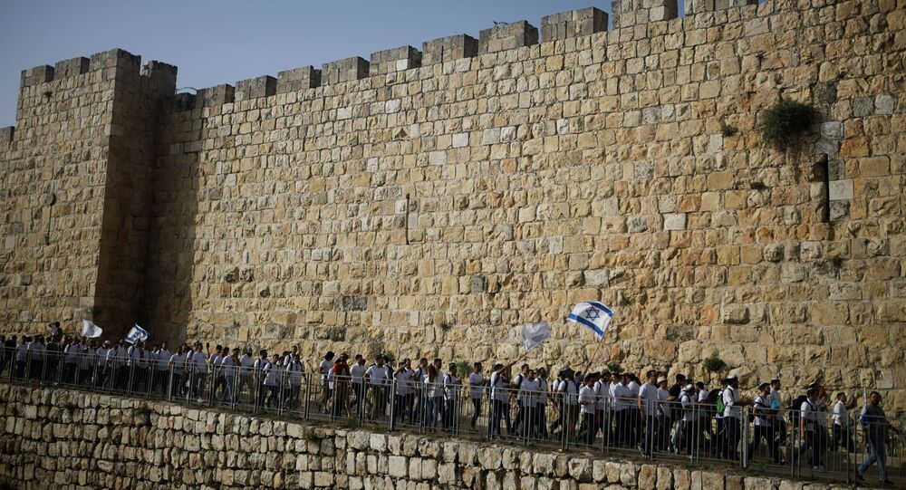 Youths wave Israeli flags during a parade marking Jerusalem Day amid Israeli-Palestinian tension as they march along the walls surrounding Jerusalem's Old City, May 10, 2021. REUTERS/Nir Elias/File Photo