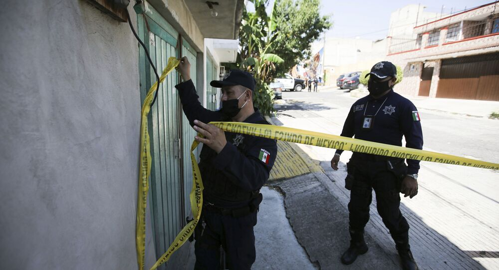 A police officer marks a security perimeter around the house where bones were found under the floor in the Atizapan municipality of the State of Mexico, Thursday, May 20, 2021. Police have turned up bones and other evidence under the floor of the house where a man was arrested for allegedly stabbing a woman to death and hacking up her body.