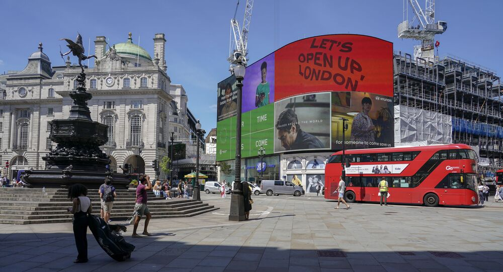People walk in Piccadilly Circus, in London, Monday, June 14, 2021