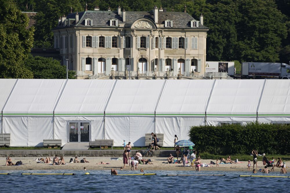 People swim on the shores of Lake Geneva in front of a tent that was set up as a media centre opposite the 'Villa La Grange' in Geneva, Switzerland Monday, 14 June 2021.