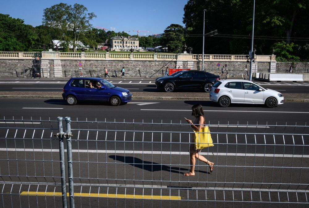 A woman walks near Villa La Grange on 14 June 2021 in Geneva, ahead of the 16 June summit between Russian leader Vladimir Putin and US President Joe Biden.
