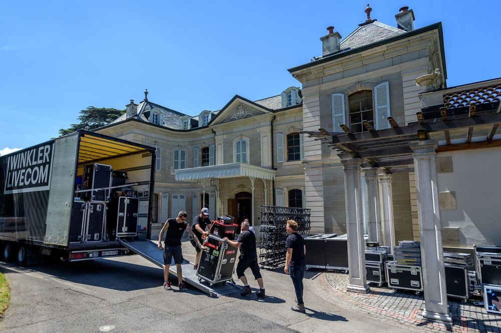 Workers carry equipment on 11 June 2021 at the entrance of Villa La Grange in Geneva, where US President and Russian President will have their meeting.
