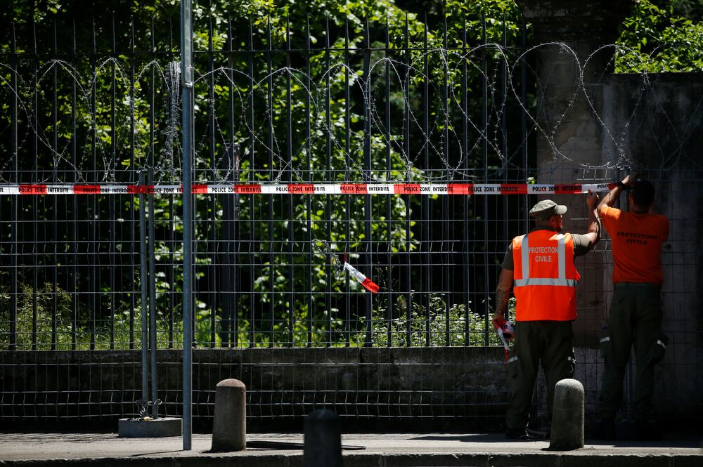 Members of civil protection check the fence outside Villa La Grange ahead of the 16 June summit.