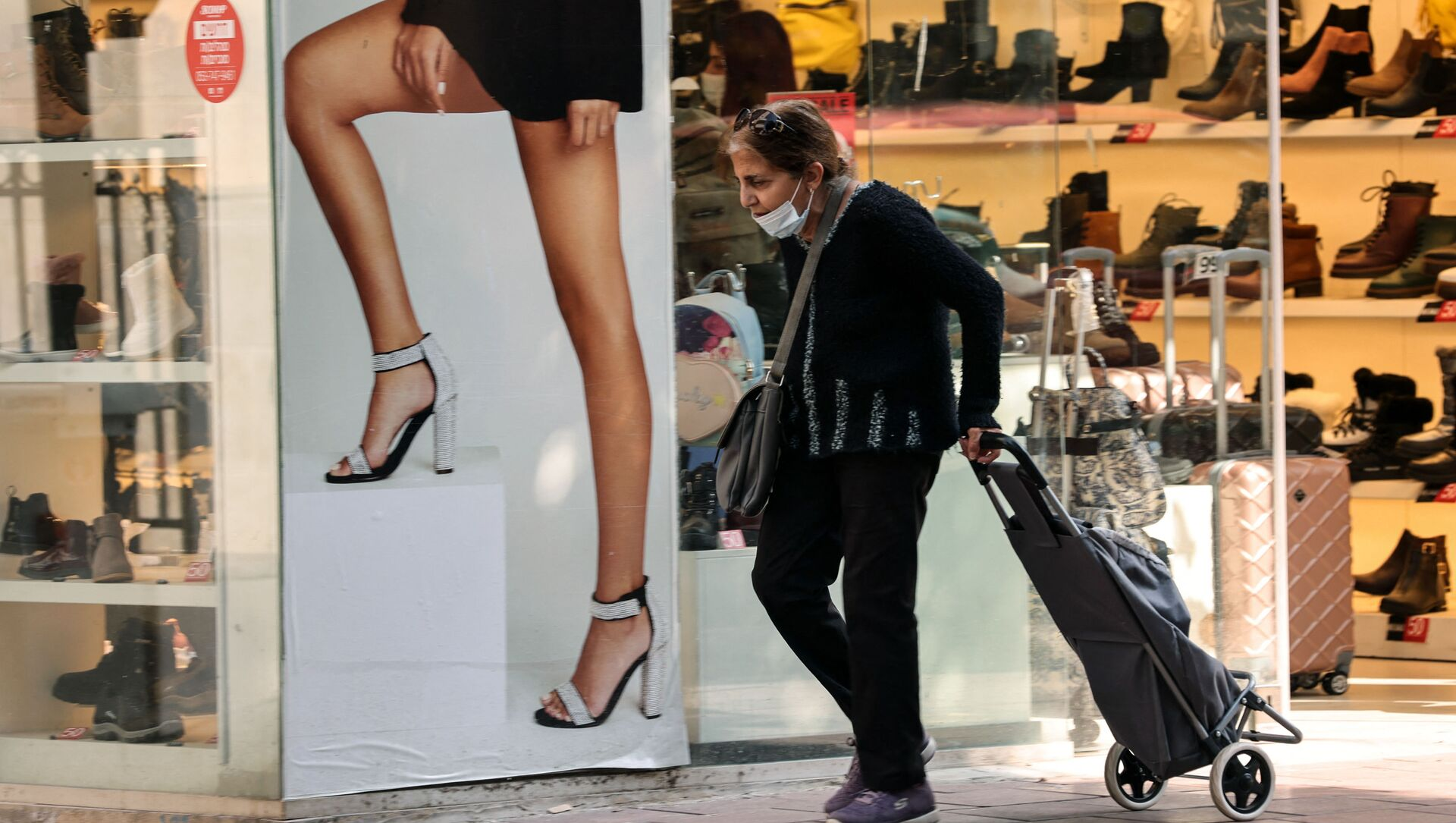 A woman walks past an open shoe store in the Israeli coastal city of Tel Aviv on February 7, 2021, following the lifting of a nationwide lockdown due to the COVID-19 pandemic.  - Sputnik International, 1920, 15.06.2021