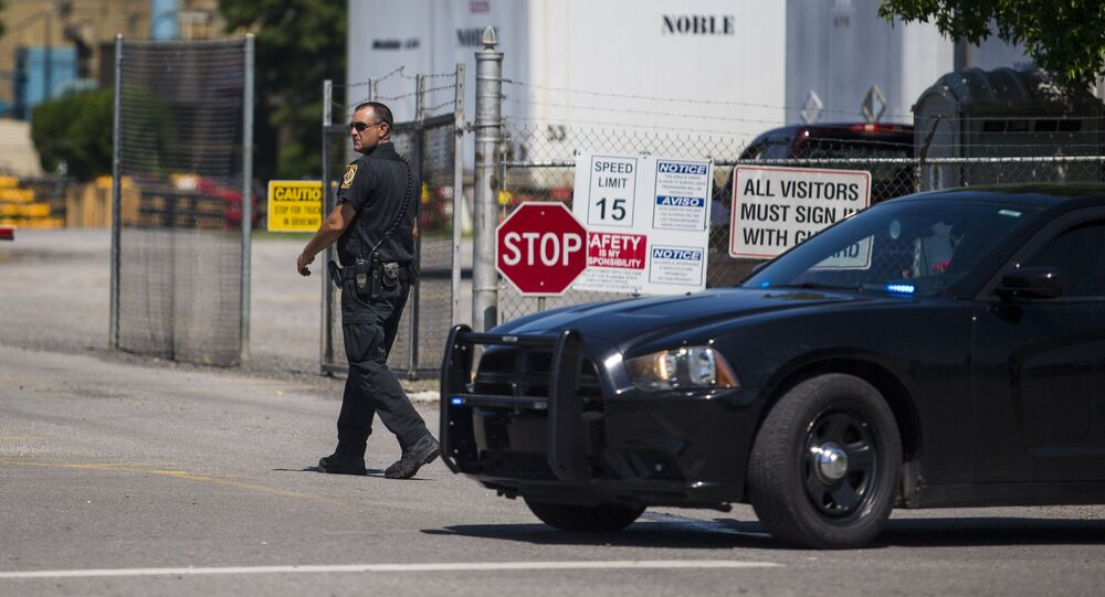 A police officer walks at the entrance to a Mueller Co. fire hydrant plant where police said multiple people were shot to death and others were wounded in Albertville, Ala., on Tuesday, June 15, 2021