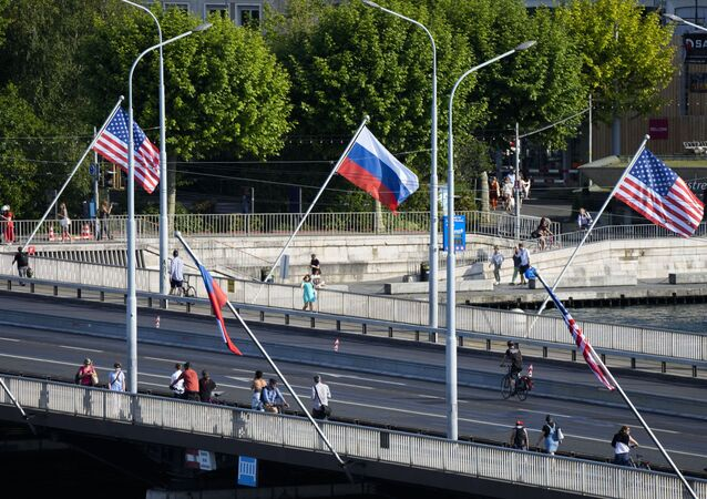 People cross a bridge decorated with United States and Russian flags in Geneva, Switzerland, Tuesday, June 15, 2021
