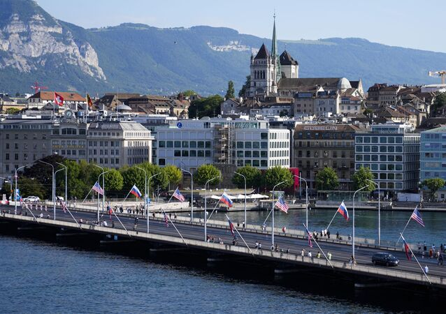 People cross a bridge decorated with United States and Russian flags in Geneva, Switzerland, Tuesday, June 15, 2021. US President Joe Biden is scheduled to meet with Russian President Vladimir Putin in Geneva, Wednesday, June 16, 2021