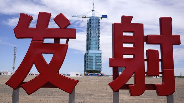 The Shenzhou-12 spacecraft sits covered on a launch pad near Chinese characters reading Launch at the Jiuquan Satellite Launch Center near Jiuquan, China on Wednesday, June 16, 2021 - Sputnik International