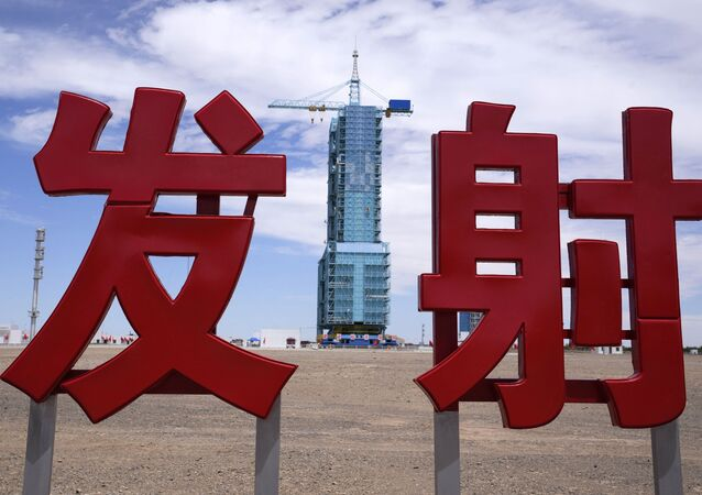 The Shenzhou-12 spacecraft sits covered on a launch pad near Chinese characters reading Launch at the Jiuquan Satellite Launch Center near Jiuquan, China on Wednesday, June 16, 2021