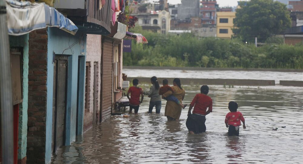 Nepalese people walk towards their flooded houses on the bank of the Bagmati river (File)