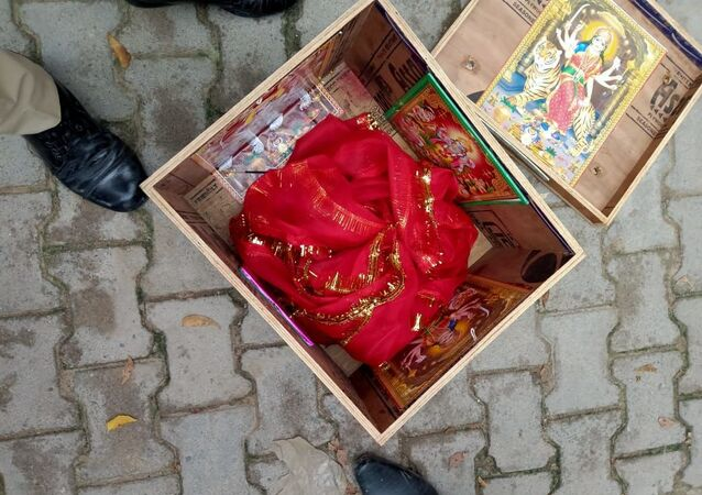 Still of a wooden box with pictures of Hindu deities on it and a red cloth that was wrapped around the abandoned newborn baby