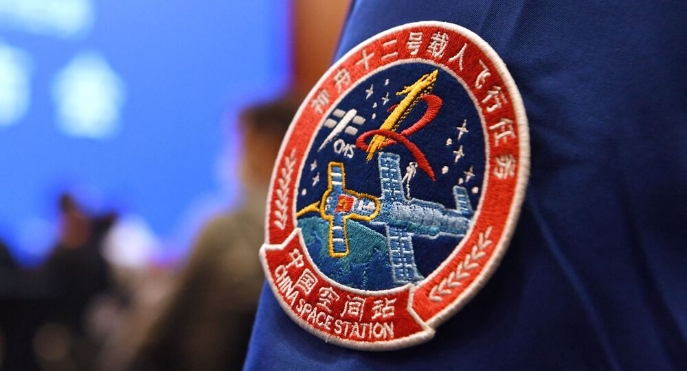 A staff member of the Jiuquan Satellite Launch Centre wears the logo of China's new space station during a press conference about the first crewed mission to the station, scheduled for June 17, at the Jiuquan Satellite Launch Centre in the Gobi desert in northwest China on June 16, 2021.