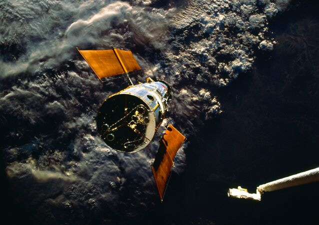 Shuttle Arm Reaches Out to Capture Hubble Space Telescope