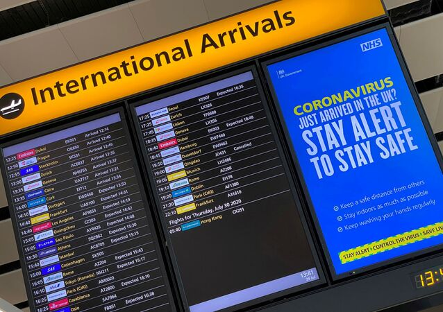 A public health campaign message is displayed on an arrivals information board at Heathrow Airport, following the outbreak of the coronavirus disease (COVID-19), London, Britain, 29 July 2020